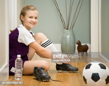 Girl (10-11) wearing football boot sitting on floor, smiling, portrait