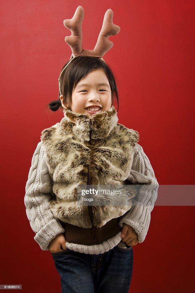 Girl wearing fur vest and reindeer ears