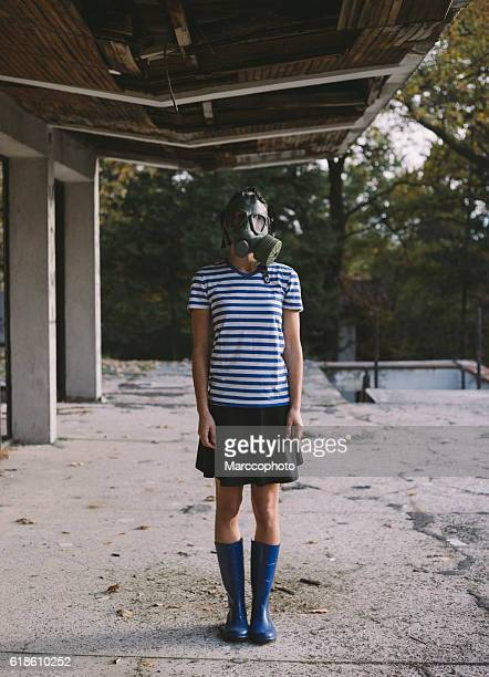 Girl wearing gas mask standing on balcony of ruined building