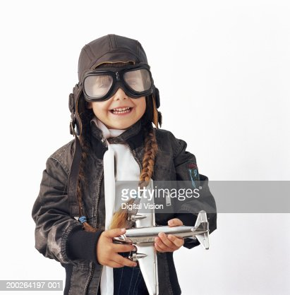 Girl (3-5) wearing goggles holding toy aeroplane, smiling, portrait