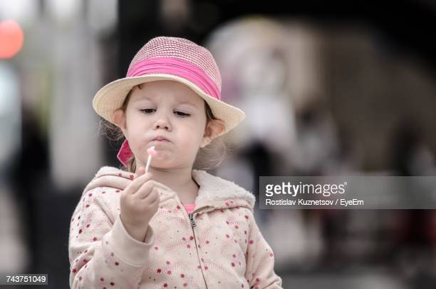 Girl Wearing Hat While Looking At Lollipop