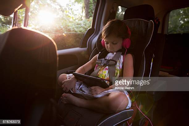 Girl wearing headphones using digital tablet in car back seat