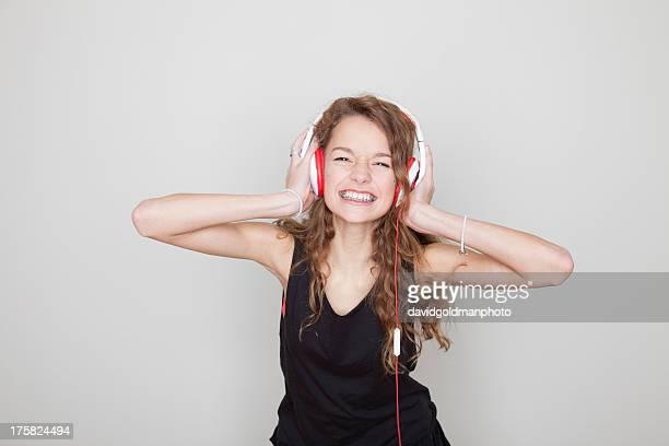 Girl wearing headphones with hands over ears