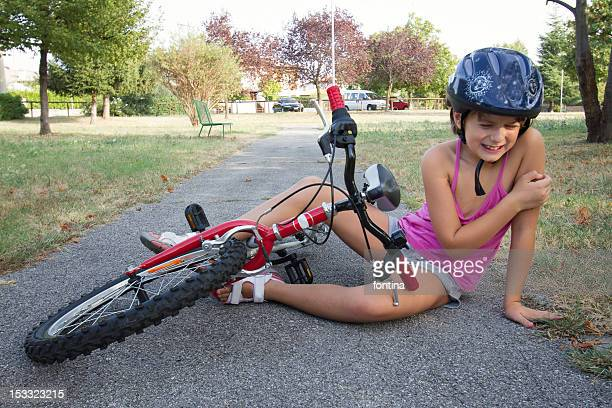 Girl wearing helmet  fallen with her  cycle