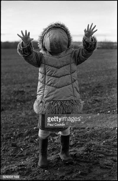 Girl wearing her coat backwards with her hands out
