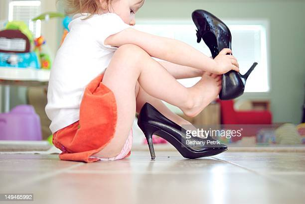 Girl wearing her mommys high heels shoes