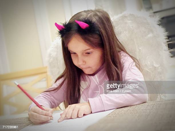 Girl Wearing Horned Headband While Studying At Home