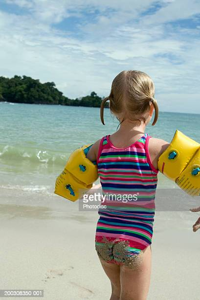 Girl (6-7), wearing inflatable arm-bands on beach