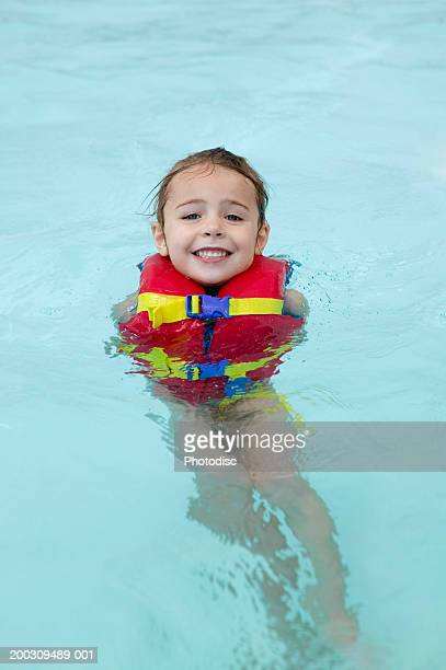 Girl (6-7), wearing inflatable life jacket in swimming pool, elevated view, portrait