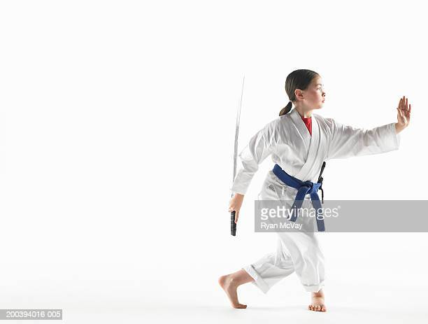 Girl (8-10) wearing karate uniform, holding Kempo sword in pose