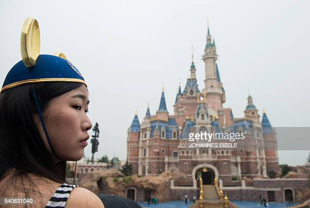 A girl wearing Mickey Mouse ears watches the opening ceremony of the Shanghai Disney Resort in Shanghai on June 16 2016 Entertainment giant Disney...