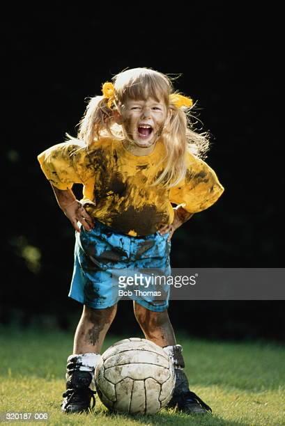 Girl (3-5) wearing muddy football kit, ball at feet, shouting