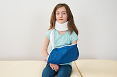 Portrait Of Girl Wearing Neck Brace And Arm Sling