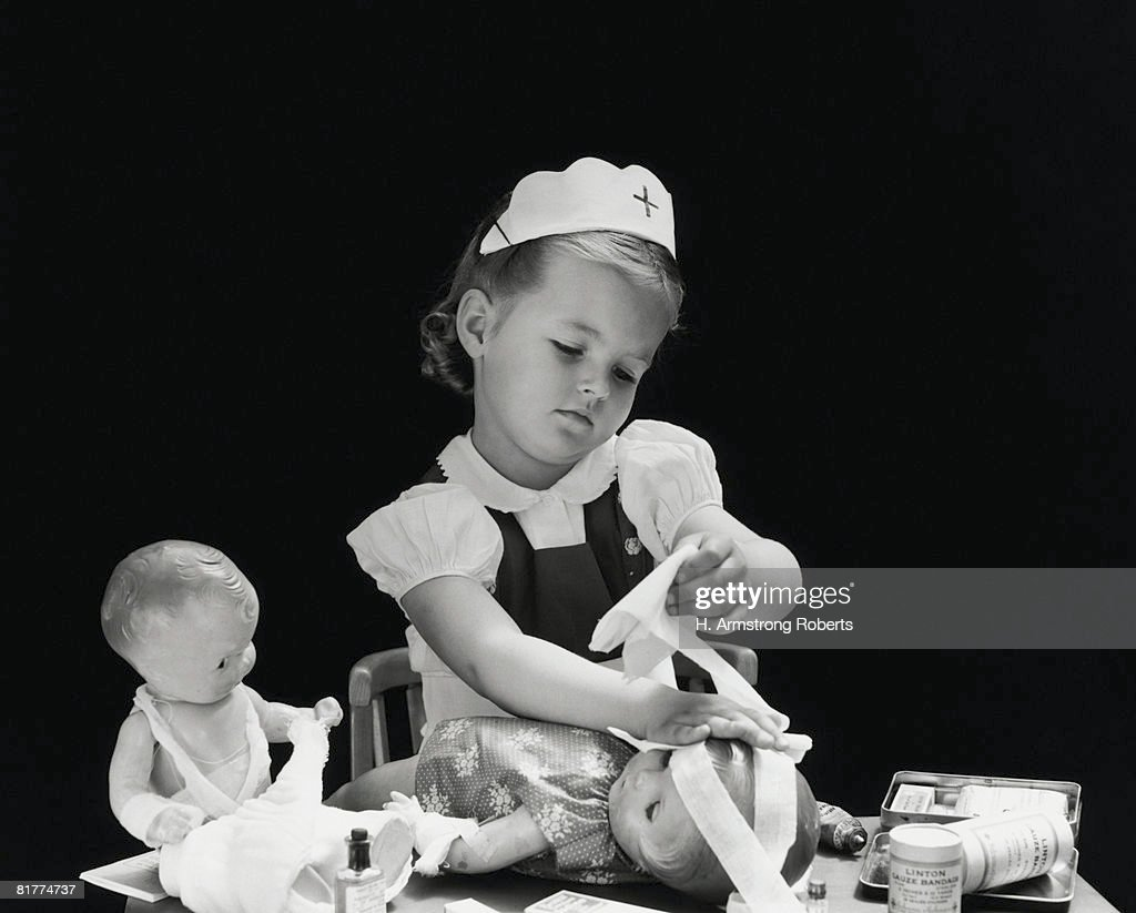 Girl wearing nurse's cap, putting bandages on doll's head. : Stock Photo