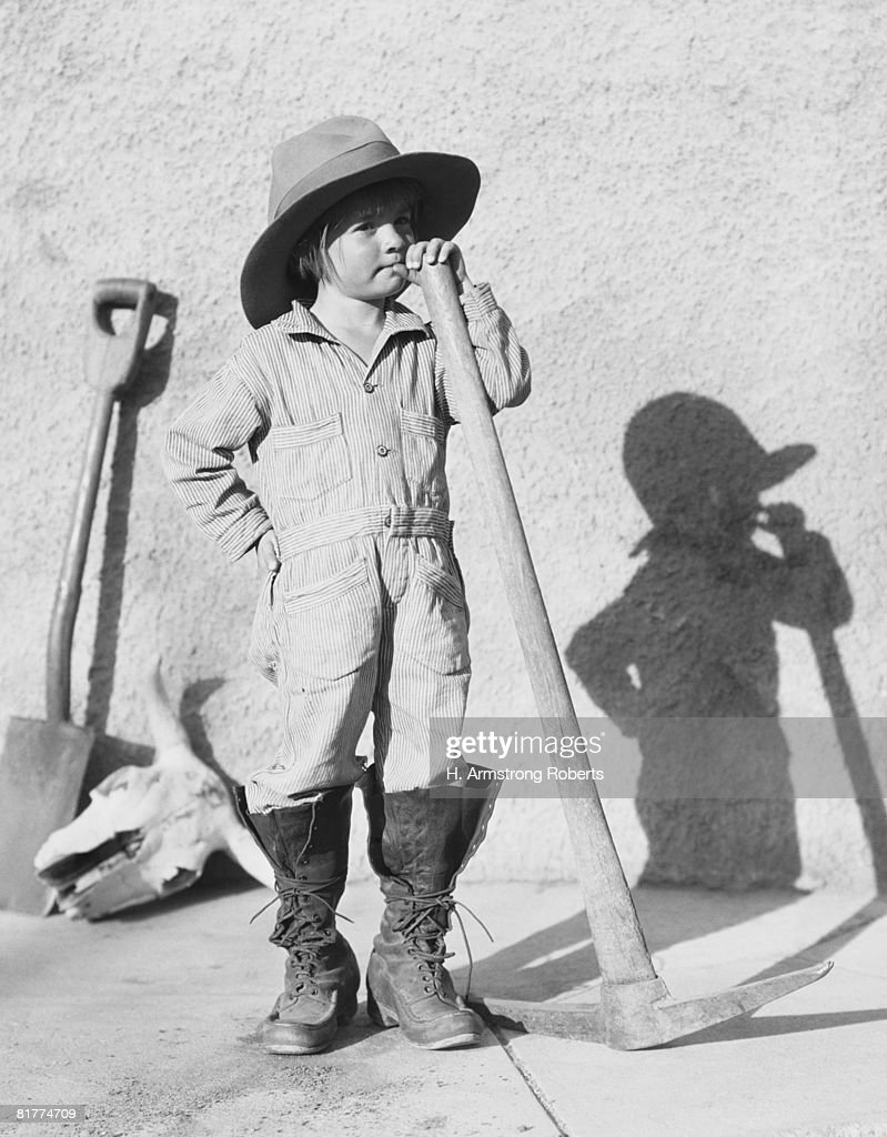Girl wearing overalls, holding pick and shovel, portrait. : Stock Photo