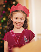 Girl (5-7) wearing paper crown, smiling, portrait