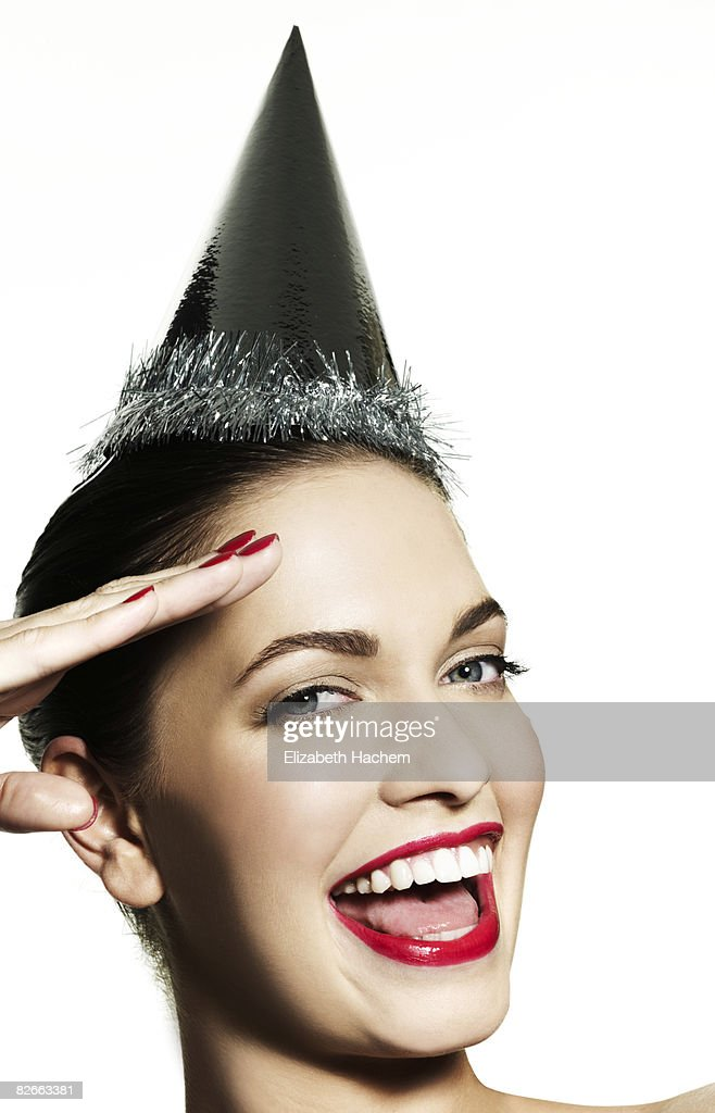 Girl wearing party hat saluting camera : Stock Photo