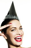 Girl wearing party hat saluting camera