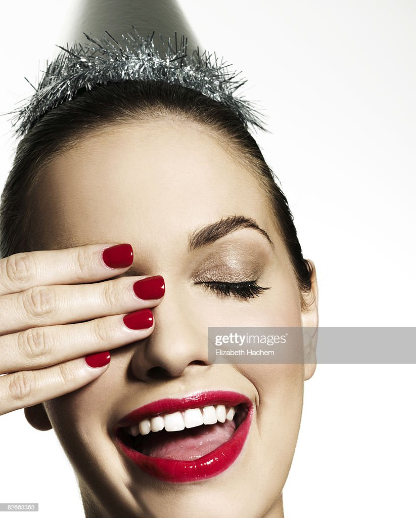 Girl wearing party hat with hand over right eye : Stock Photo