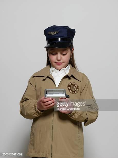 Girl (7-9) wearing pilot's cap, looking at digital image on camera