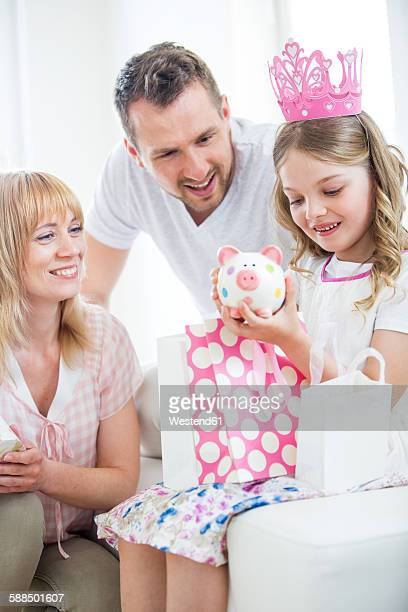 Girl wearing pink crown holding gift bags, parents watching