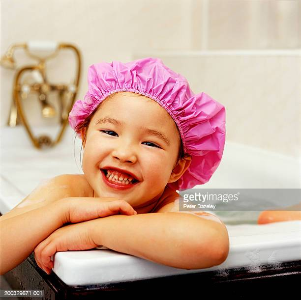 Girl (3-5) wearing pink shower cap, smiling, close up, portrait