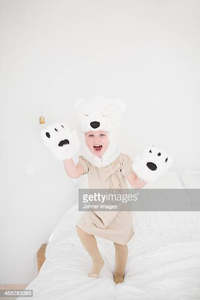 Girl wearing polar bear costume jumping on bed