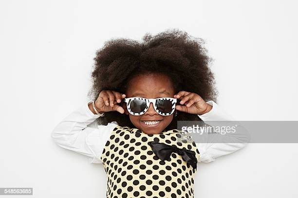 Girl wearing polka dot dress and sunglasses, close up