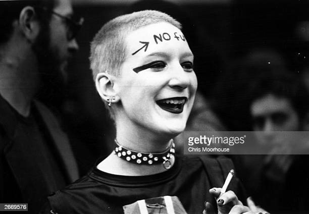 A girl wearing punk clothes and make up including the words 'No Future' across her forehead waiting outside the Rainbow Theatre London before a Jam...