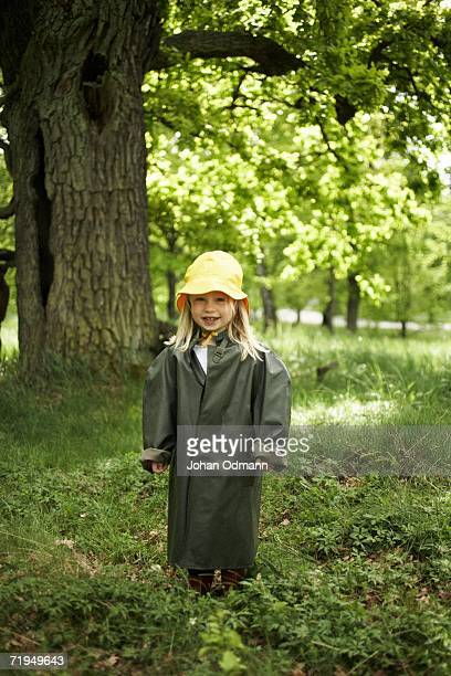 Girl wearing rain clothes in the forest.