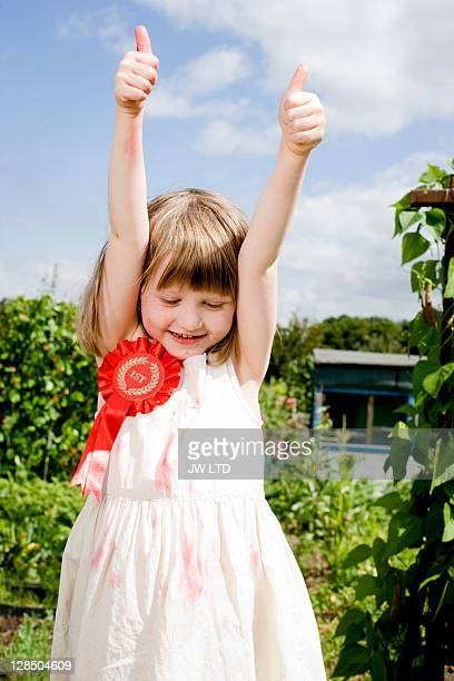 Girl wearing rosette with thumbs up
