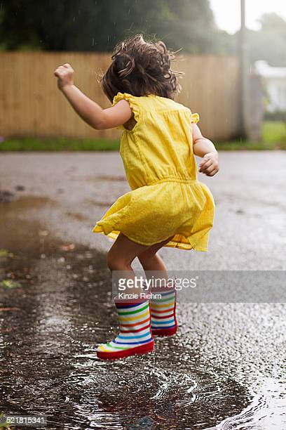 Girl wearing rubber boots jumping in rain puddle