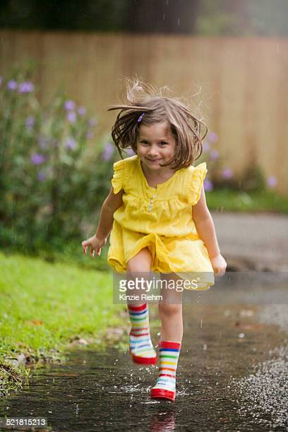 Girl wearing rubber boots running in rain puddle