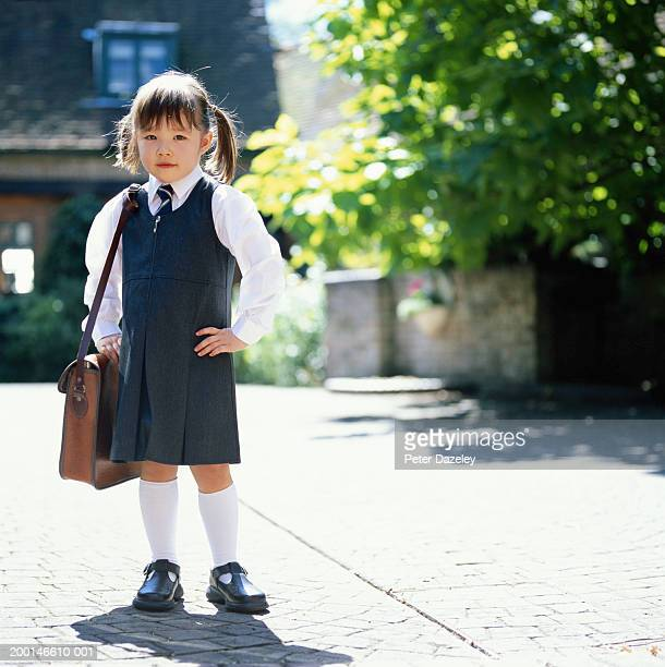 Girl (3-5) wearing school uniform, holding bag, outdoors, portrait