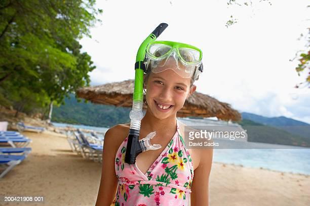 Girl (10-12) wearing snorkel gear smiling, portrait