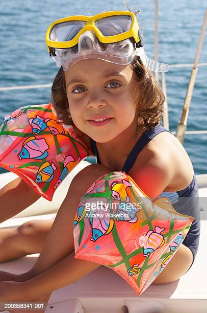 Girl (4-5 years) wearing snorkling mask and armbands on yacht