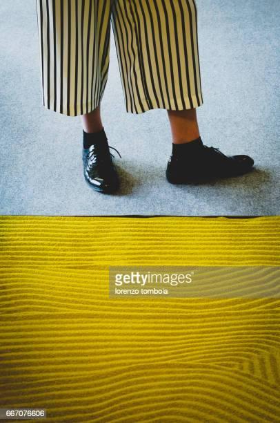 Girl wearing stripy pant close to zen garden, close-up