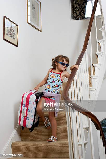 Girl (3-5) wearing sunglasses carrying suitcase down stairs, smiling