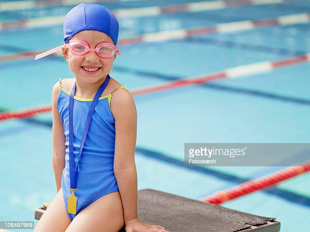 Girl wearing swimming goggles by pool (portrait)