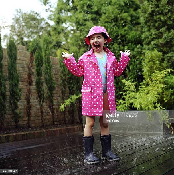 Girl (4-6) wearing  swimsuit and raincoat in rain