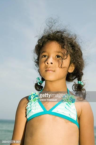 Girl (4-6) wearing swimsuit at beach, looking upwards