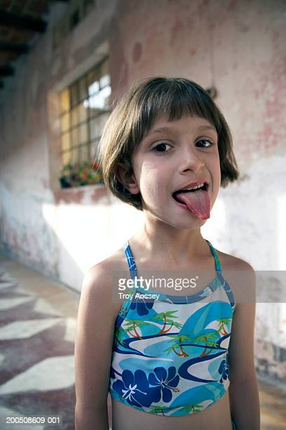 Girl (6-8) wearing swimsuit, sticking out tongue, portrait