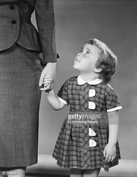 Girl wearing  tartan plaid dress with white trim, holding her mother's left hand with her right hand while looking up at her inside.