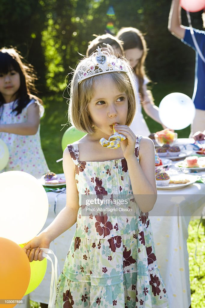 Girl wearing tiara and blowing party horn blower at outdoor party