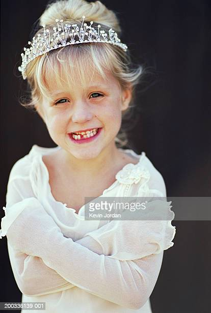 Girl (4-6) wearing tiara, arms crossed, smiling, close-up, portrait