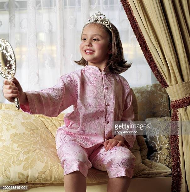 Girl (4-6) wearing tiara, looking in hand mirror