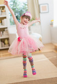 Girl (4-5) wearing tutu dancing in living room, Jersey City, New Jersey, USA