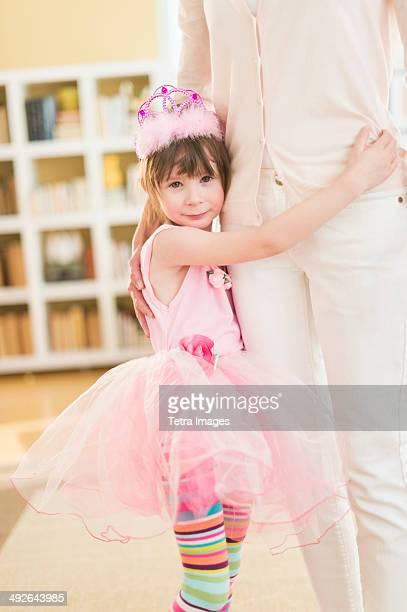 Girl (4-5) wearing tutu holding onto mother, Jersey City, New Jersey, USA