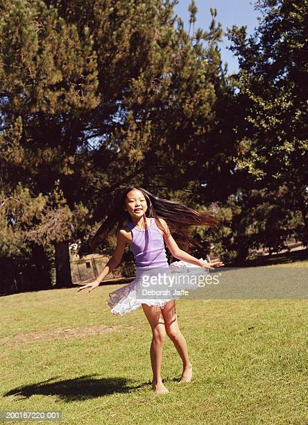 Girl (9-11) wearing tutu, spinning outdoors, portrait