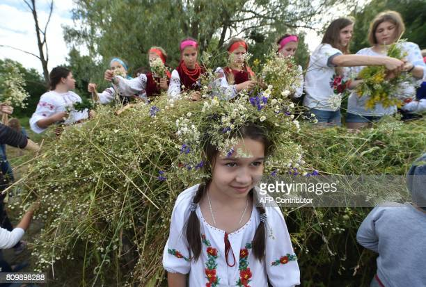 A girl wearing Ukrainian traditional clothes poses for a photograph as others collect flowers to make wreaths during the celebrations of Ivana Kupala...
